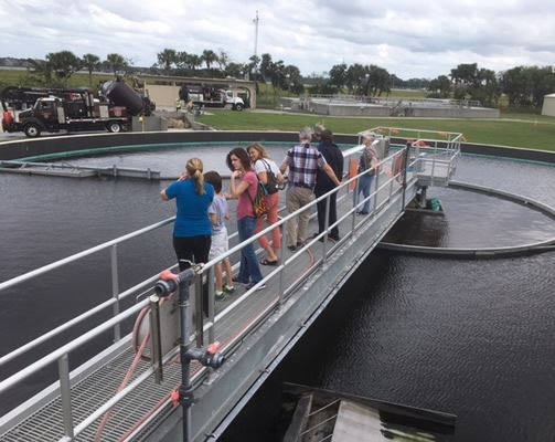 People on the clarifier catwalk at the wastewater treatment plant
