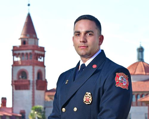 Headshot photo of Fire Chief Carlos Aviles with Flagler College tower in the background