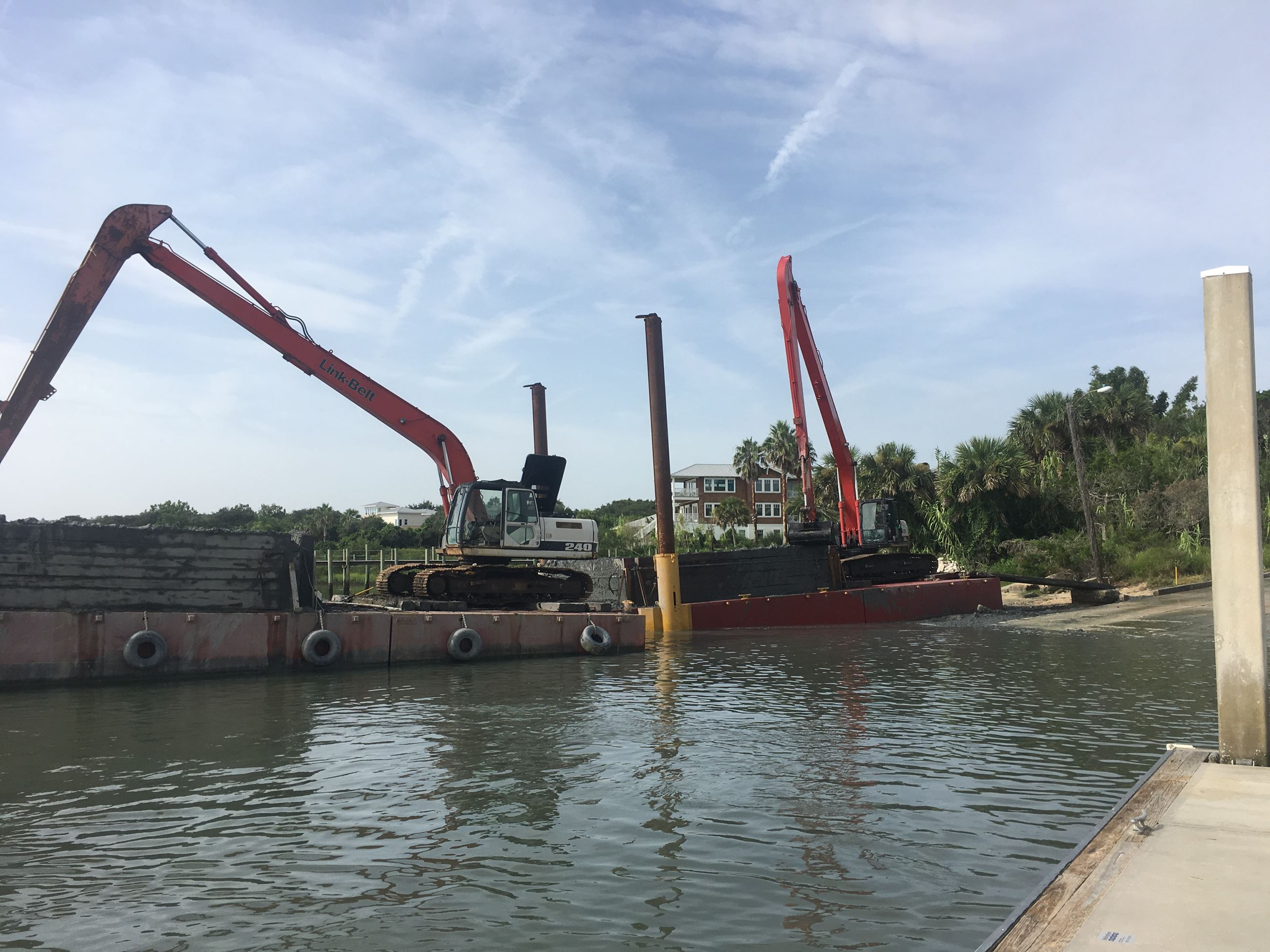 backhoe and crane equipment on a barge near a boat ramp