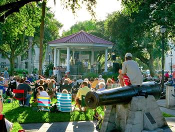 Concert in the Plaza with people sitting around in chairs on the lawn